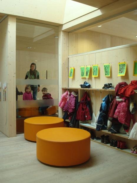 Общо пространство за преобличане и преобуване с поглед към занималня през стъклени стени
